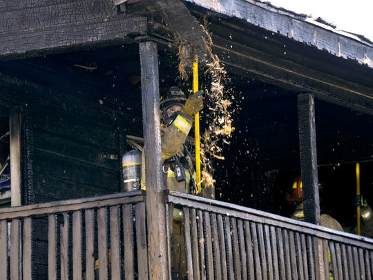 An Abilene firefighter chips away at the balcony roof