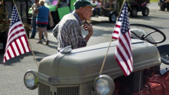 Tim Santry of Northfield checks out tractors parked before the start of the annual Labor Day parade in Northfield on Monday, September 1, 2014.
