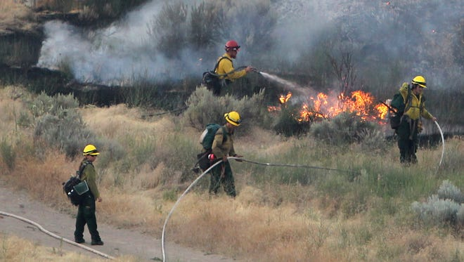 In this June 30, 2016, file photo, firefighters respond to a wildfire near the Morningside Heights neighborhood near Table Rock in east Boise, Idaho.