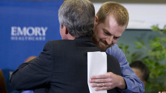 Ebola victim Dr. Kent Brantly, right, hugs a member of the medical staff that treated him, after being released from Emory University Hospital Thursday, Aug. 21, 2014, in Atlanta. Another American aid worker, Nancy Writebol, who was also infected with the Ebola virus, was released from the hospital Tuesday.