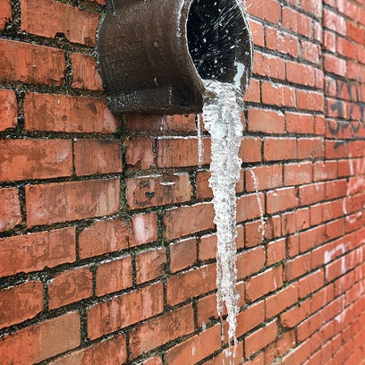 Icicles hang from a down spout as melting water splashes