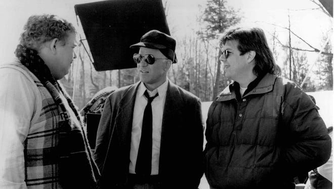 "Writer/producer/director John Hughes (right) discusses a scene with Steve Martin  (center) and John Candy on location in  ""Planes, Trains and Automobiles."" The movie is an uproarious cross-country comedy about two hilarious mismatched traveling companions experiencing Murphy's Law of American transportation while traveling to Chicago for the Thanksgiving holiday."