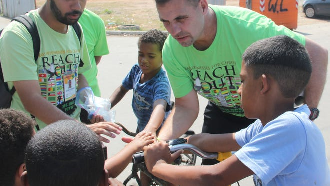 Randy Shepherd, right, visits with children at one of the slums in Rio.