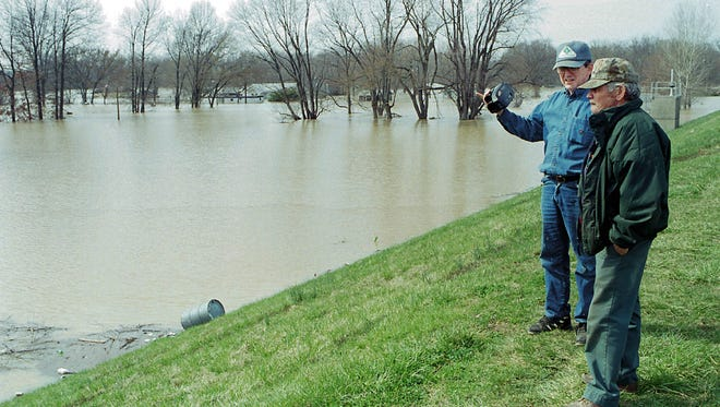 Uniontown residents Jimmy Duncan (L) and Buddy Girten stand on the towns flood wall and lookout over the flood waters last year covering the section of town outside of the flood wall.