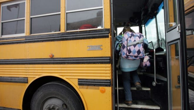 A student boards a school bus.