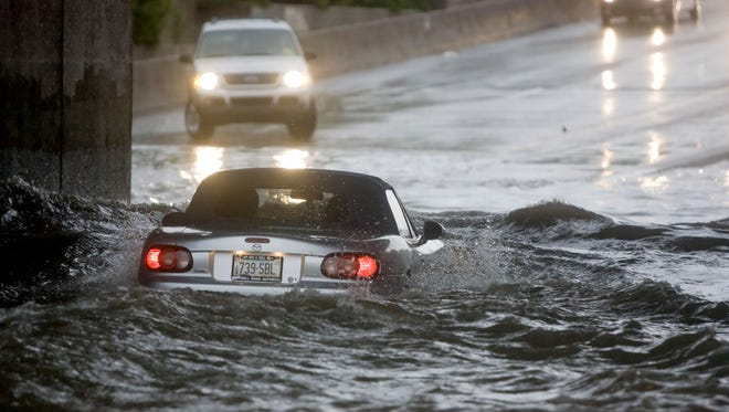 Floodwater nearly engulfs a car on McClintock Drive in Tempe during a storm.