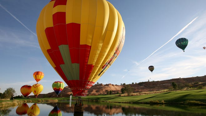 Hot air balloons rise over the Lake Powell National Golf Course during the Page / Lake Powell Hot Air Balloon Regatta, Saturday, Nov. 1, 2008.