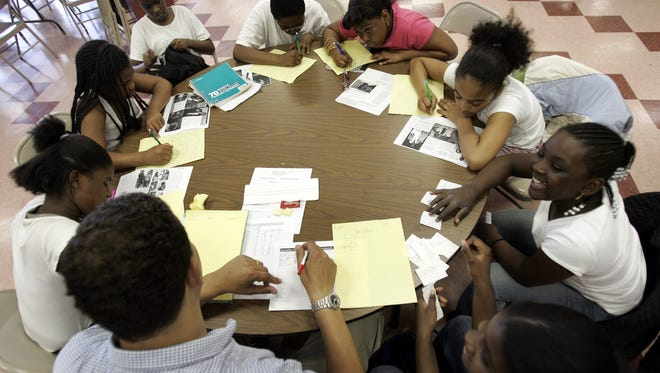 Girls work with school counselor Henry Walker on a reading project at the Nepperhan Community Center in Yonkers May 19, 2006. The center's programs are designed to give youth wholesome alternatives to violence or gang activity in the surrounding neighborhood.
