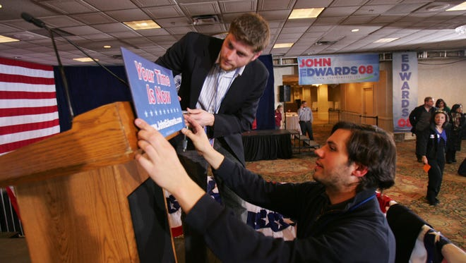 John Edwards campaign staffers Dan Secatore, left, and Eric Soufer place a sign on the podium at the Renaissance Savery Hotel in 2008. Campaign staffers and media have filled up hotels in downtown Des Moines ahead of the 2016 caucus.