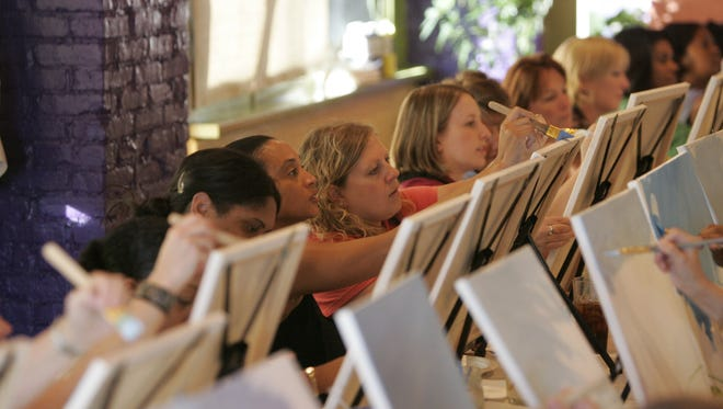 Wine & Canvas customers at work in Indianapolis in 2010. The Indianapolis location has filed for bankruptcy after it was hit with a large jury verdict.