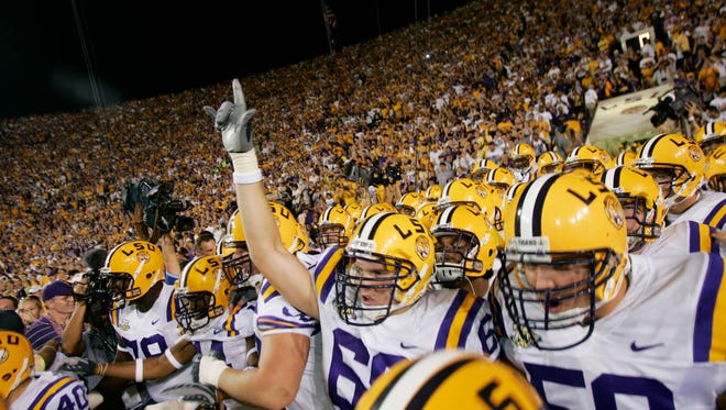 LSU players run out on to the field at Tiger Stadium.