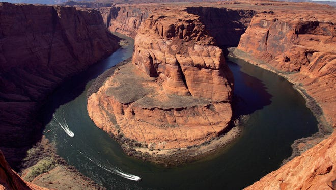 In this March 5, 2008 file photo, boats skirt the shore at the Colorado River's Horseshoe Bend, downstream from the Glen Canyon Dam, in Page, Ariz. In a new critique by the Colorado River Research Group, environmental protection for the 1,450-mile-long Colorado River, the lifeblood of the American Southwest, is disjointed and too often takes a back seat to to other needs.