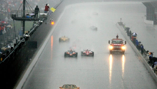 Checkered and yellow flags wave as Dario Franchitti (left), winner of the 91st running of the Indianapolis 500, crosses the finish line under caution as the race ended after 166 of the 200 laps when a heavy downpour hit the track.   fell at the track on Sunday, May 27, 2007. Finishing second was Scott Dixon, to Franchitti's right, and behind them were Helio Castroneves third and Sam Hornish Jr., fourth.