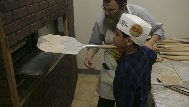 Rabbi Bernstein works with Lidor Guzi in putting the matzoh in the oven to bake at Chabad Lubavitch in Marlboro in this 2008 file photo.