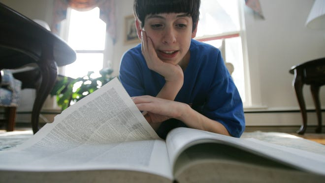 David Tidmarsh, 2004 winner of the National Spelling Bee, thumbs through the dictionary he studied to help him to victory.  A South Bend native, Tidmarsh is in the ninth grade.  He studied everyday for a year, 3 hours daily on weekdays and 4 hours daily on weekends. /// 2_INSpellingBee.#112118 Photo by Adriane Jaeckle, Star Staff 04/25/2005