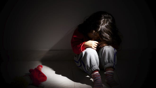 A file photo of a child curled up in the dark. A Nevada lawmaker is proposing courts take a favorable view of sexually assaulted or trafficked children who hurt or kill their abusers.