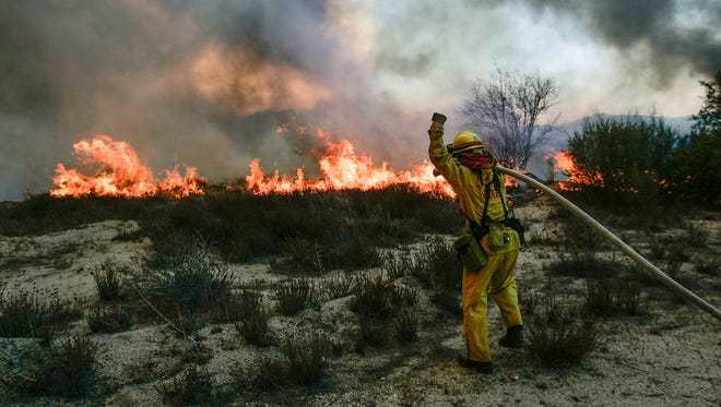 A firefighter battles the Esperanza Fire near Poppet Flats, October 26, 2006.