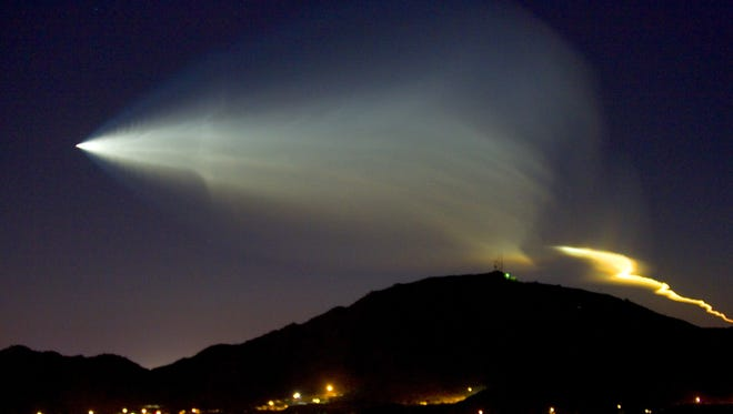 The contrail from rocket carrying a satellite into space lights-up the western sky over North Mountain in Phoenix.