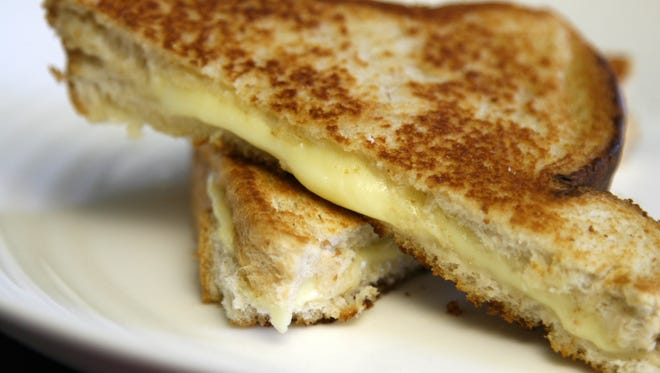 Melting grilled cheese sandwich on white plate