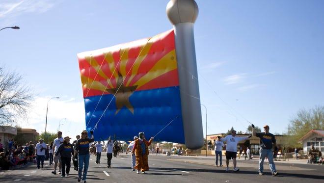 A huge Arizona flag balloon floats down Scottsdale Road at the 2012 Parada del Sol Parade. Arizona celelbrates its 105th birthday this year.