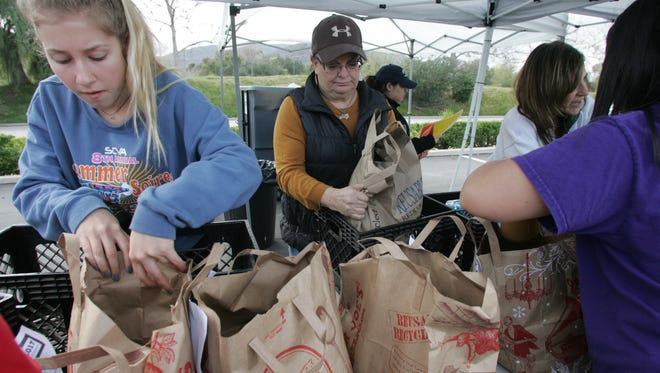 In this file photo, volunteer Blair Beaumont and Jennifer Schwabauer, executive director of Manna Conejo Food Bank, transfer donated food into crates at The Oaks mall in Thousand Oaks as part of the annual Scouting for Food drive.