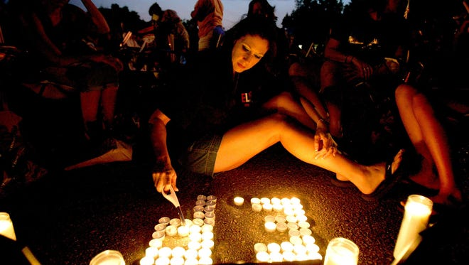 "August 15, 2009 - Trisha Polinard, of Sante Fe, Texas, lights candles in the form of Elvis Presley's initials on Elvis Presley Boulevard just before the annual vigil for Presley began. This was Polinard's seventh consecutive year at Elvis Week, which her family makes a vacation out of. It was her first year attending with out her mother, Patsy Valdez, who ""is in heaven with Elvis.""  Elvis Presley died at Graceland on Aug. 16, 1977."