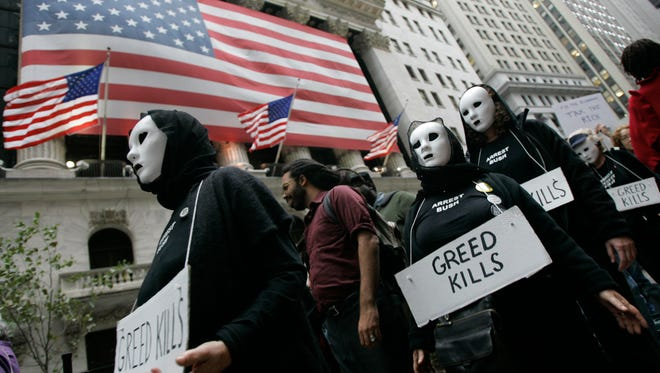 Protestors march past the New York Stock Exchange during a rally against the Wall Street bailouts, Thursday, Sept. 25, 2008