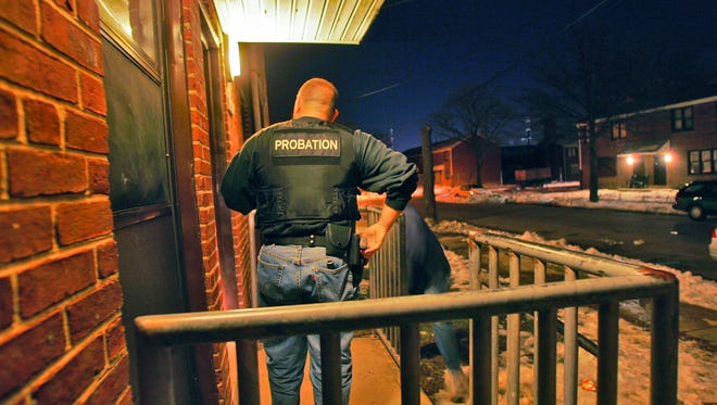 """Officer Tim Dean checks whether a juvenile offender on probation is home in time for curfew in Riverside. The probationer, who lives with his aunt, was not home. """"He just left out of here,"""" his aunt says."""