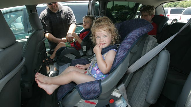 Star file photo from when state law required booster seats for kids up to age 8, effective July 1, 20015. Dad Gary Ford straps his son Marcus Ford into a car seat in the family van with siblings Alyssa Ford and Jakob Ford after a trip to the zoo.