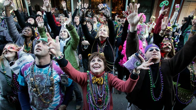 Revelers beg for beads to be tossed from a balcony in the French Quarter during Mardi Gras day  in New Orleans, Louisiana. The annual Mardi Gras celebration on Feb. 13 ends at midnight, when the Catholic Lenten season begins on Ash Wednesday and ends on Easter Sunday.