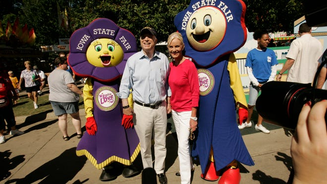 Sen. John McCain (left) and his wife, Cindy, pose for photos with the State Fair mascot ribbons Fairfield, right, and Rosetta Aug. 8, 2008 at the Iowa State Fair in Des Moines. The Republican presidential candidate and his wife visited the largest boar, ate a pork chop on  a stick and saw the butter cow display after speaking at the Des Moines Register soapbox.