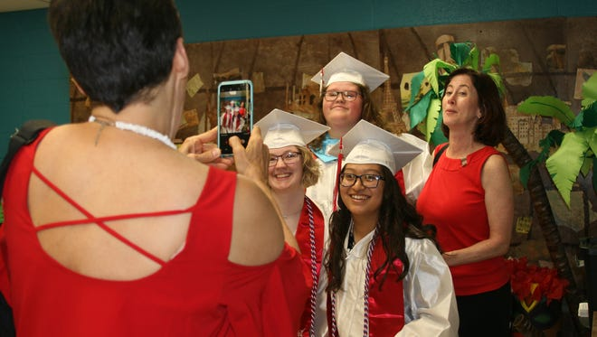 Flippin High School graduates Ashley Vredenburg and Maria Paz (front row from left) pose with Kayleigh Warren and German and English teacher Jennifer Metts (back row) while getting ready to walk for Friday night's ceremony.