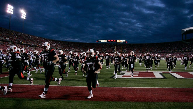 Louisville players run off the field before a game against Connecticut at Papa John's Stadium.