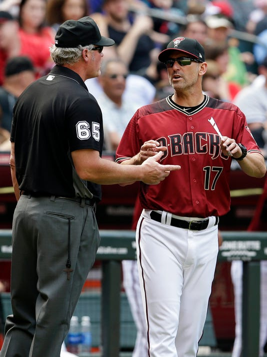 Arizona Diamondbacks manager Torey Lovullo (17) talks to umpire Ted Barrett (65) about a replay in the seventh inning during a baseball game against the Cleveland Indians, Sunday, April 9, 2017, in Phoenix. (AP Photo/Rick Scuteri)