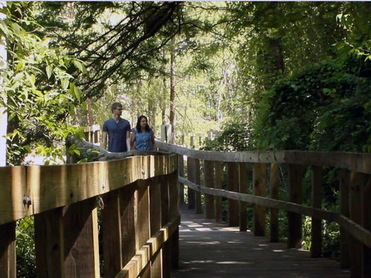 A couple strolls down the boardwalk that meanders a quarter mile through the bottomland hardwoods of the Cypress Island Preserve at Lake Martin.