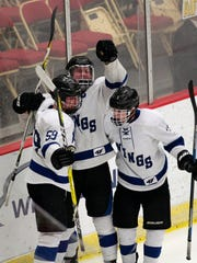 Waukesha's Ian Malcolmson (59) and Trenton Tucker (12)  celebrate the power play goal of Wyatt Wilderma (25).