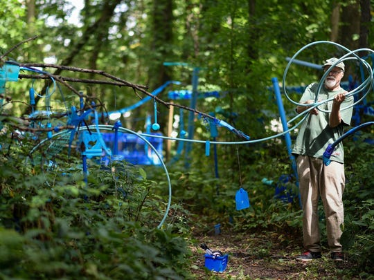 In this Aug. 30, 2018 photo, artist Robert Park works on The Blue Loop,a 1,000-foot art installation on his property in Bath Township, Mich. Public support has helped Park keep his outdoor art installation after officials initially ruled that the thousands of found objects violated an anti-junk ordinance.