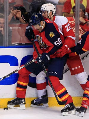 Florida Panthers right wing Jaromir Jagr (68) and Detroit Red Wings left wing Drew Miller (20) battle for control of the puck in the third period at BB&T Center.