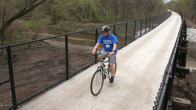 Riders cruise along the newly-paved bridge at Mally's park in Berwick on the Chichaqua Trail heading toward Bondurant on April 18, 2015.