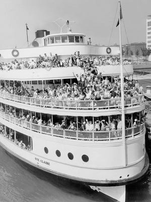 Happy cruisers wave on the Boblo boat Ste. Claire along the Detroit waterfront.