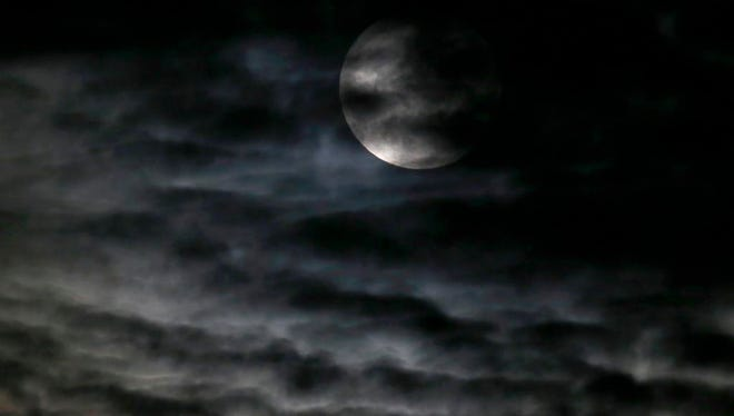 Clouds obscure the so-called supermoon before a lunar eclipse Sunday, Sept. 27, 2015, in Chicago. It's the first time the events have made a twin appearance since 1982, and they won't again until 2033.
