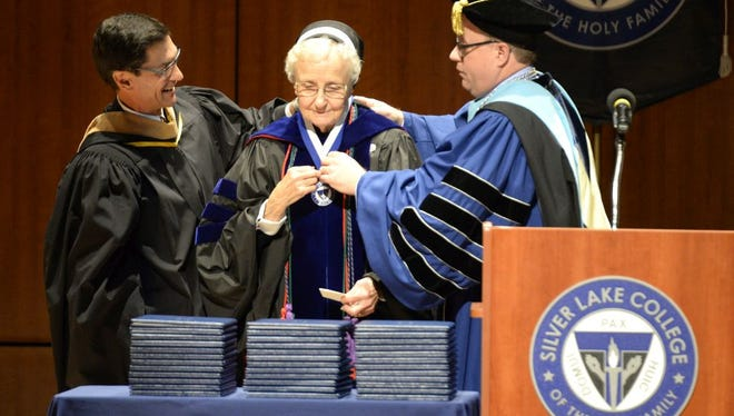 Eric B. Volcheff, chairman of the Silver Lake College Board of Trustees, left, and Dr. Chris E. Domes, president of Silver Lake College, right, present Sister Michaela Melko with her professor emeritus medallion during the Winter Commencement Ceremony Dec. 17.