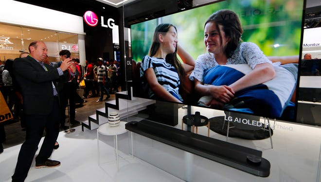 CES 2018 attendees view the LG signature OLED 4K HDR Smart TV at the LG Electronics booth during the 2018 International CES.