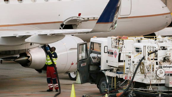 A worker prepares to fuel a United Express aircraft