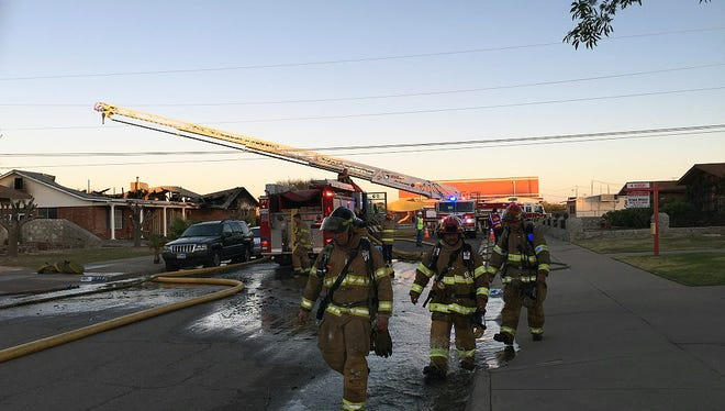 El Paso firefighters walk away after battling a blaze Wednesday in the 8900 block of Dirk Court in East El Paso.