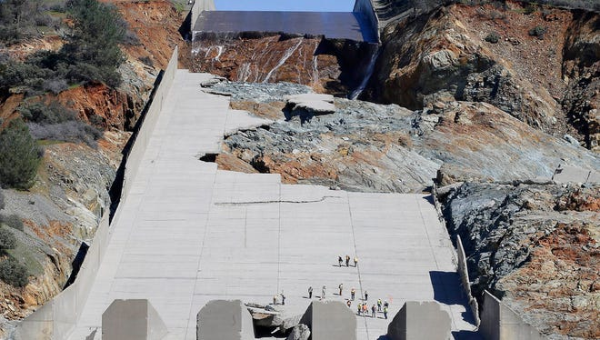 In this Feb. 28, 2017 file photo, officials inspect Oroville Dam's crippled spillway in Oroville, Calif. California is asking owners of about 70 aging dams, some dating back to the Gold Rush, to thoroughly inspect their spillways and underlying rock, as part of stepped-up inspections in the wake of the surprise spillway failures at the nation's highest dam.