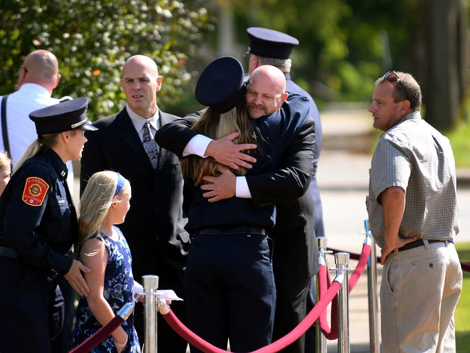 Firefighters and others hug outside Gorsline Runciman