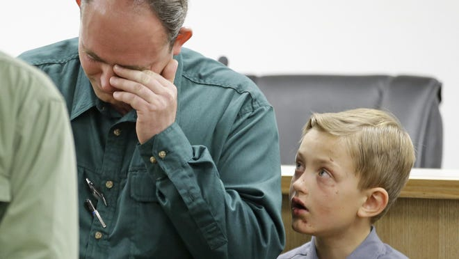 Sheldon Black, Jr., lowers his head as one of his two surviving sons looks on during a news conference Thursday, Sept. 17, 2015, in Colorado City, Ariz. Black expressed his gratitude for the outpouring of support after his wife and children were swept away in a flash food Monday.