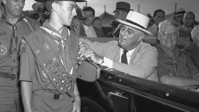 """FILE - This July 8, 1937 file photo, President Franklin D. Roosevelt stops briefly to pin an Eagle Badge, highest honor of """"scoutdom"""" on the chest of Franklyn C. St. John, 17, of Poughkeepsie, N.Y., at the jamboree camp in Washington. The Boy Scouts of America has filed for bankruptcy protection as it faces a barrage of new sex-abuse lawsuits. The filing Tuesday, Feb. 18, 2020, in Wilmington, Del., is an attempt to work out a potentially mammoth compensation plan for abuse victims that will allow the 110-year-old organization to carry on. (AP Photo, File)"""
