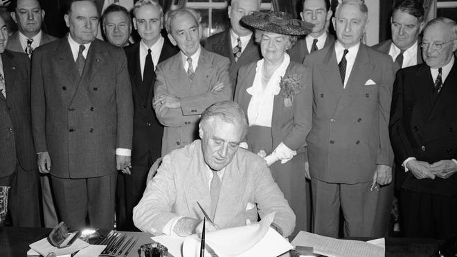 President Franklin D. Roosevelt puts his signature on the G.I. Bill of Rights at the White House, putting into law the measure for veterans aid June 22, 1944. Looking on from left to right are: Sen. Bennett Clark (D-Mo.); Rep. J. Harbin Peterson (D-Fla.); Rep. A. Leonard Allen (D-La.); Rep. John Rankin (D-Miss.); Rep. Paul Cunningham (R- Ia.); Rep. Edith Nourse Rogers (R-Mass.); J.M. Sullivan; Sen. Walter George (D-Ga.); John Steele; and Sen. Robert Wagner (D-N.Y.). Sullivan and Steele are American Legion officials who helped sponsor the bill.
